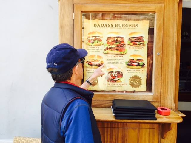 The Travel Curmudgeon in Malta reviewing a restaurant menu featuring the Obama Burger, with numerous indecisive toppings!